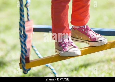 Enfant debout sur la balançoire, low section Banque D'Images