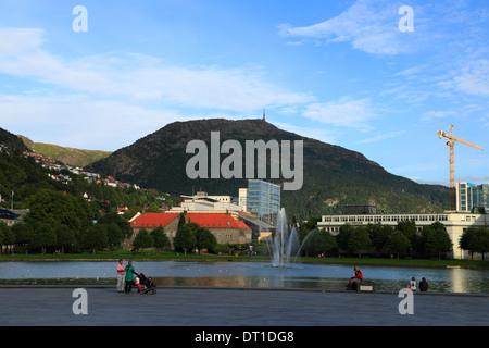 Vue sur Lille Lungegårdsvannet vers le mont Ulriken en ville Bergen, en Norvège, où les gens se rassemblent au bord de l'eau au cours d'une soirée d'été. Banque D'Images