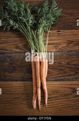 Un petit bouquet de carottes avec les tops freshly harvested allongé sur une table Banque D'Images