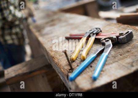 Atelier de bois d'une terre d'une personne à un établi et des outils et pinces pinces alignés sur une planche de Banque D'Images