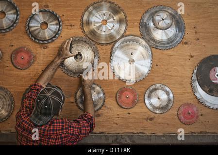 Un atelier de bois d'un homme régénéré atteignant jusqu'à un conseil de stockage pour lames de scie circulaire pour Banque D'Images