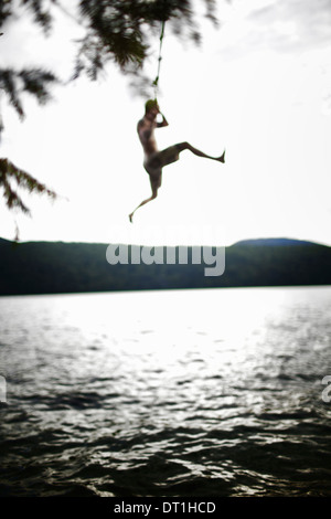 Boy Jumping off rope swing Banque D'Images