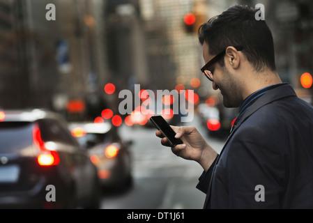 Un homme en veste sombre contrôler son téléphone cellulaire sur une rue animée au crépuscule Banque D'Images