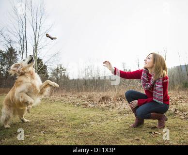 Une jeune femme à l'extérieur l'hiver sur une marche avec un golden retriever dog