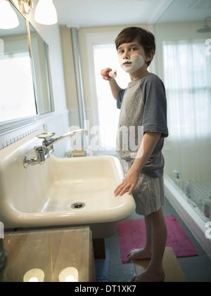 Un jeune garçon se tenant dans une salle de bains avec une brosse de rasage couvrant son visage avec de la mousse Banque D'Images