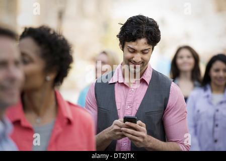 Les gens à l'extérieur dans la ville au printemps un homme regardant son téléphone cellulaire Banque D'Images