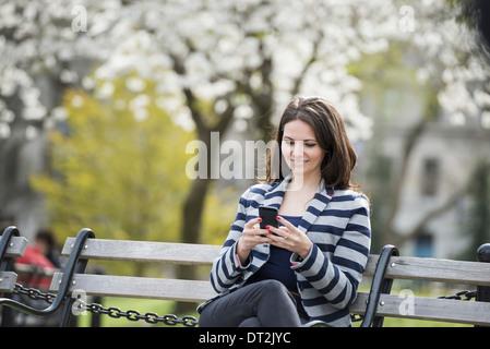 Spring Time New York City park White blossom sur les arbres une femme assise sur un banc tenant son téléphone mobile Banque D'Images