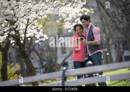 New York City park un homme et une femme côte à côte, de prendre une photo avec un téléphone cellulaire tenu en Banque D'Images