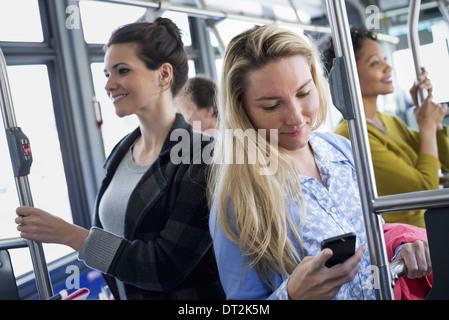 La ville de New York les hommes et les femmes sur un bus de transport public dans le contrôle d'une jeune femme Banque D'Images