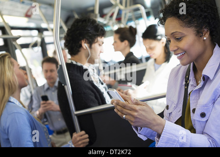 New York City bus de la ville, hommes et femmes, dans le transport public une jeune femme contrôler ou à l'aide Banque D'Images