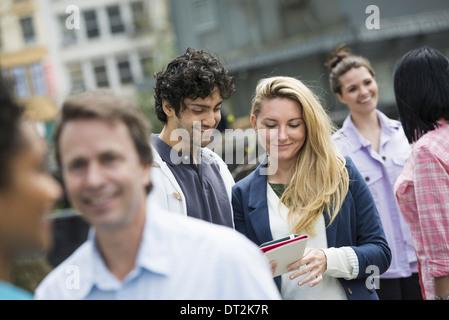 Un couple au centre à la recherche à un téléphone cellulaire Banque D'Images