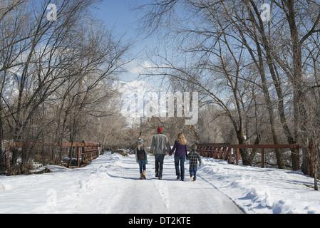 Paysage d'hiver avec neige au sol une famille adultes et deux enfants marchant sur une route vide Banque D'Images
