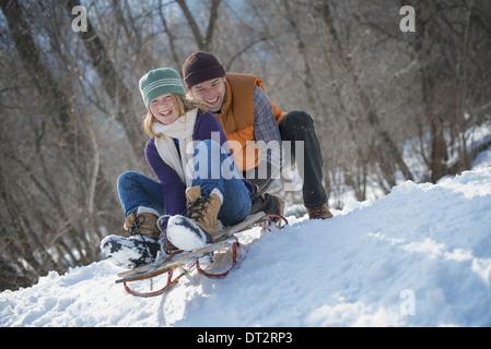 Paysage d'hiver avec neige au sol un homme poussant une jeune femme du haut d'une pente sur un toboggan