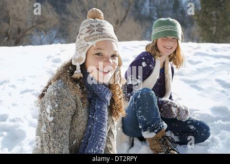 Paysage d'hiver avec neige au sol une femme et un enfant assis sur le sol en riant