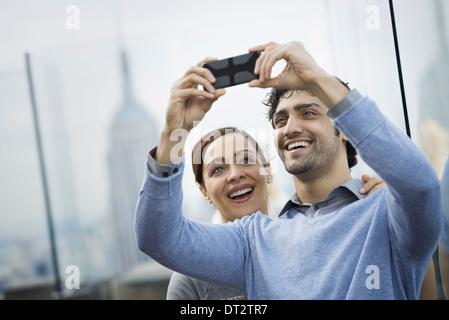Vue sur Ville jeune couple à prendre des photos avec un téléphone mobile Banque D'Images