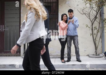 Les jeunes des rues au printemps un couple de prendre des images d'eux-mêmes en utilisant un téléphone intelligent Banque D'Images