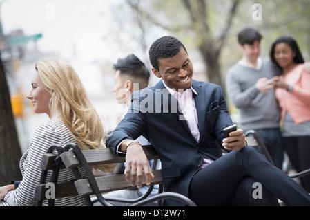 Vue sur Ville réunis autour d'un banc de parc Deux contrôler un téléphone intelligent pour les messages Banque D'Images
