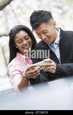 Vue sur cityYoung les gens à l'extérieur dans un parc de la ville un couple côte à côte en regardant un téléphone Banque D'Images