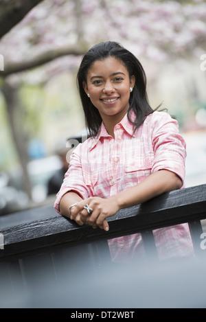 Vue sur cityA jeune femme aux cheveux noirs portant une chemise rose à la recherche sur une balustrade et smiling