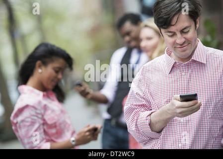 Vue sur cityYoung les gens à l'extérieur dans un parc de la ville trois personnes contrôler en regardant leur téléphone Banque D'Images