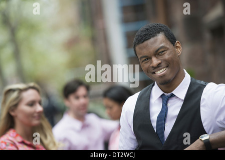 Vue sur cityYoung les gens à l'extérieur dans un parc de la ville un homme souriant à la caméra trois personnes Banque D'Images