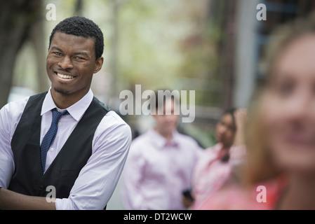 Vue sur cityYoung les gens à l'extérieur dans le parc de la ville un homme les bras croisés de sourire et de trois Banque D'Images