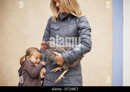 Une femme tenant un poulet noir et blanc avec une croix rouge coxcomb sous un bras une jeune fille à côté d'elle Banque D'Images