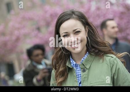 Cerisiers dans le parc une jeune femme en chemise à col ouvert souriant et regardant la caméra