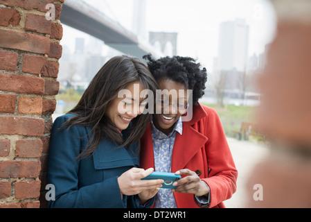 Passage sur le pont de Brooklyn, l'East River, deux femmes côte à côte, contrôler l'écran d'un téléphone intelligent Banque D'Images