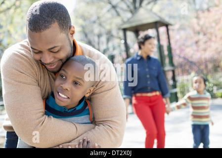 Une famille les parents et les deux garçons de passer du temps ensemble un père serrant son fils Banque D'Images