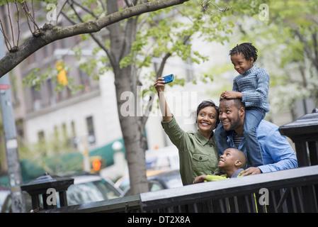 Un garçon à cheval sur les épaules de son père et d'une femme à l'aide d'un téléphone intelligent de prendre une photo selfy