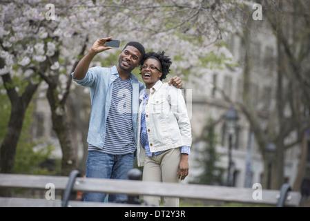 Un couple côte à côte de prendre une photo avec un téléphone intelligent Banque D'Images