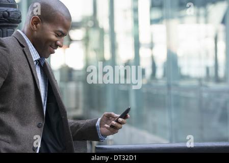 Un homme debout à l'extérieur contrôler son téléphone cellulaire Banque D'Images