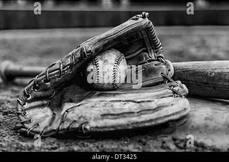 Jours de gloire de baseball avec balle dans la main et bat sur base sur terrain. Image Monochrome avec mur extérieur Banque D'Images