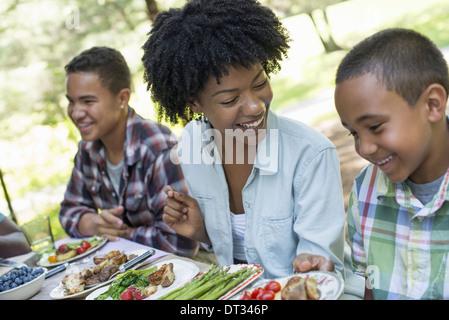 Un pique-nique en famille dans un bois ombragé une femme et deux garçons assis laughing Banque D'Images