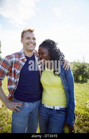 Un couple d'un jeune homme et une femme côte à côte en riant Banque D'Images