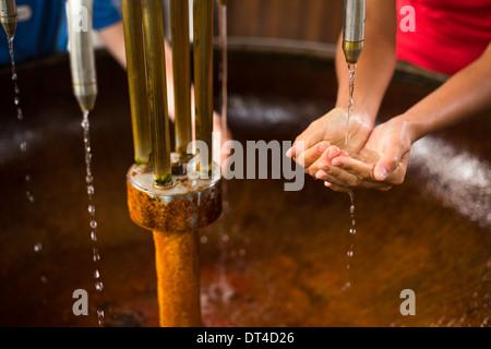 Personnes remplissant les mains avec de l'eau minérale en bonne santé à partir d'une source dans un spa (shallow Banque D'Images