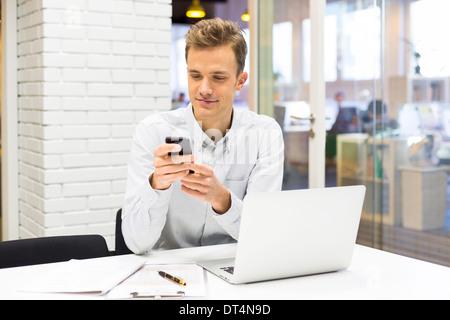 24 l'homme l'ordinateur appelant téléphone cellulaire Banque D'Images