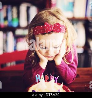 Petite fille avec la tête dans les mains à ennuyer Banque D'Images