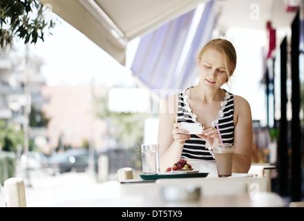 Jolie femme prendre photo d'une pâtisserie sur son mobile Banque D'Images