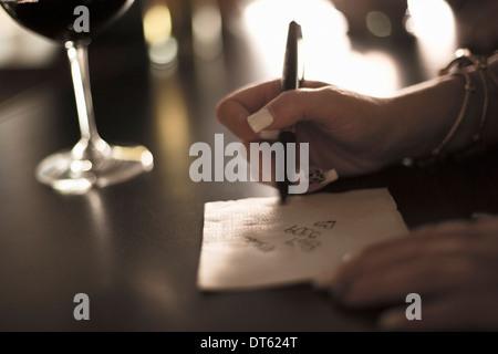 Close up of young woman écrit son numéro de téléphone sur une serviette en bar Banque D'Images