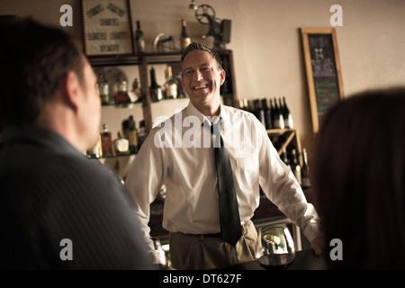 Barman à discuter avec les clients de Wine bar Banque D'Images