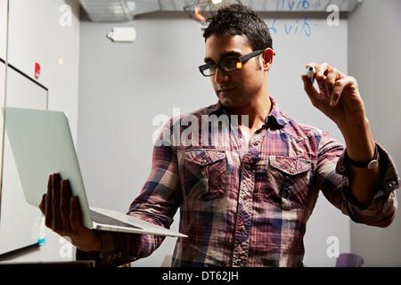 Man looking at laptop avec plume en main Banque D'Images