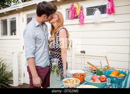 Jeune couple partageant un baiser dans jardin Banque D'Images