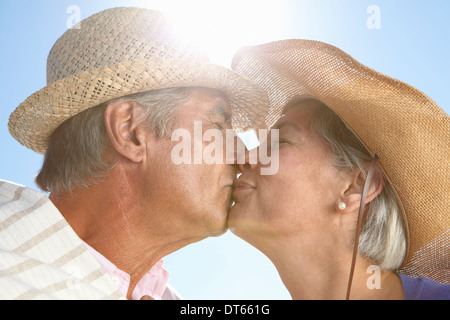 Couple wearing straw hats kissing Banque D'Images