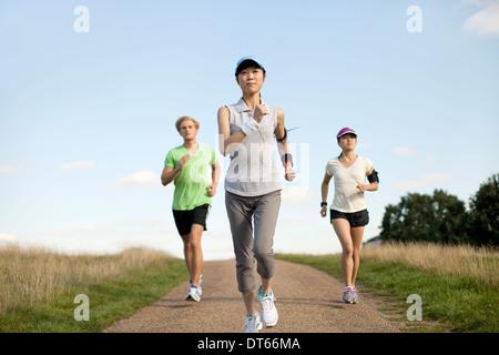 Trois jeunes adultes du jogging le long de la voie sur le terrain Banque D'Images