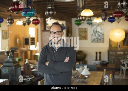 Un homme debout dans un magasin plein de meubles anciens et objets de décoration. Antique Shop s'affiche. L'éclairage, Banque D'Images