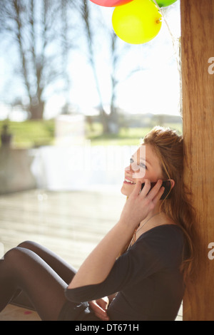 Teenage girl talking on mobile at Birthday party Banque D'Images