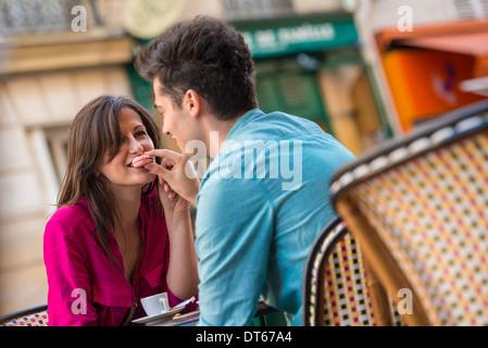 Jeune couple partageant la chaussée à macaron cafe, Paris, France Banque D'Images