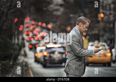 Un homme en costume contrôler son téléphone cellulaire, debout sur une rue animée au crépuscule. Banque D'Images